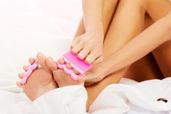 Attractive woman painting her toes in bed. Stock Photography