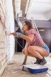 Attractive woman paints white brick wall brush Stock Photo