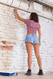 Attractive woman paints white brick wall brush Royalty Free Stock Image
