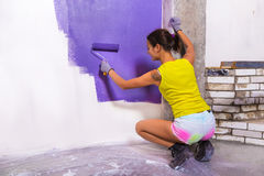 Attractive woman paints white wall purple roller Stock Images