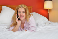 Attractive woman in pajamas in bed talking on phone Royalty Free Stock Images