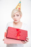 Attractive woman in party hat opening gift box Stock Photography