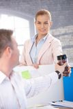 Attractive woman passing coffee to colleague Royalty Free Stock Photo