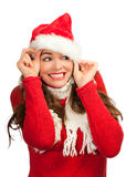 Attractive woman peeking out from santa hat Royalty Free Stock Photography