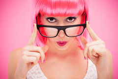 Attractive woman peeking over glasses. Woman wearing wig over pink background Stock Photos