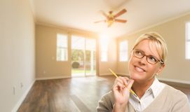 Attractive Woman with Pencil In Empty Room of House stock photos
