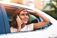 Attractive woman with phone in car, sunny day royalty free stock photos
