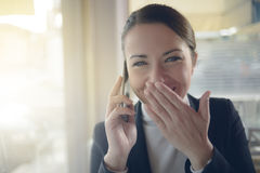 Attractive woman on the phone next to a window Stock Images
