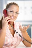 Attractive woman on the phone in office smiling. Attractive woman talking on phone in office, gesturing, smiling stock images
