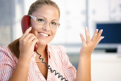 Attractive woman on the phone in office smiling. Attractive woman talking on phone in office, gesturing, smiling Stock Photos