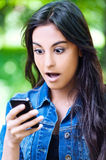 Attractive woman phone surprised. Dark-haired young attractive woman park keeps phone reads message surprised royalty free stock photo