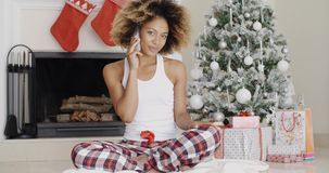 Attractive woman phoning her friends at Christmas. Attractive trendy young African woman phoning her friends or family at Christmas sitting in front of the stock footage