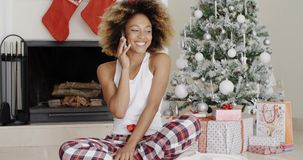 Attractive woman phoning her friends at Christmas. Attractive trendy young African woman phoning her friends or family at Christmas sitting in front of the stock video