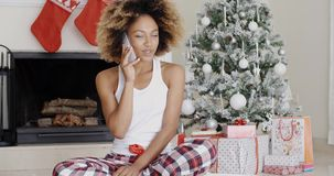 Attractive woman phoning her friends at Christmas. Attractive trendy young African woman phoning her friends or family at Christmas sitting in front of the stock video footage