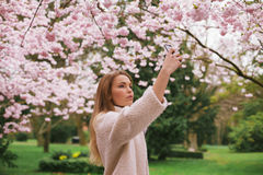 Attractive woman photographing flowers at the spring garden Royalty Free Stock Image