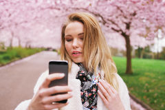 Attractive woman photographing herself at the spring garden Royalty Free Stock Photo