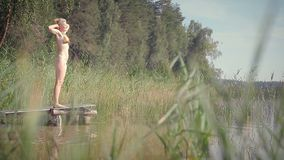 Attractive woman on the pier by the lake. She stretches and walks on the pier. The shore of the lake overgrown with reeds. The lake is located in a pine forest stock video