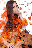 Attractive  woman in a  pile of autumn leaves Royalty Free Stock Photography