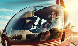 Attractive woman pilot. Sitting in the helicopter Stock Photos