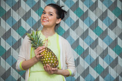Attractive woman with pineapple smile on a blue background. Happy girl hold ananas ready to make juice. Copy space Stock Photos