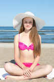 Attractive woman in pink bikini sitting on the beach. Young attractive woman in pink bikini sitting on the beach Royalty Free Stock Image