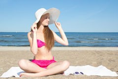 Attractive woman in pink swimsuit sitting on the beach Stock Photos