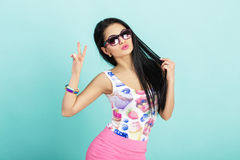 Attractive woman in pink tank top on blue background. girl in sunglasses showing two fingers or victory gesture Royalty Free Stock Images