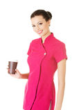Attractive woman in pink uniform holding a cup. Royalty Free Stock Photo
