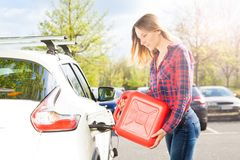 Attractive woman with plastic can filling car tank Royalty Free Stock Photo