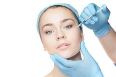 Attractive woman at plastic surgery with syringe in her face. On white background Royalty Free Stock Photos
