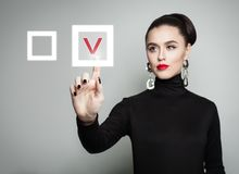 Attractive woman pointing her finger at red checkmark. In checkbox. Young businesswoman voting on gray background. Education and business concept Royalty Free Stock Images