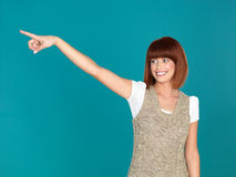 Attractive woman pointing to the left. Beautiful, young woman, smiling and pointing to the left, on blue background Stock Photo