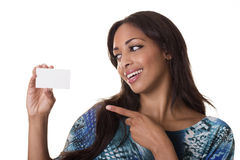 Attractive woman points to a blank business card. A pretty woman looks at a blankn business card while pointing at it Royalty Free Stock Photos