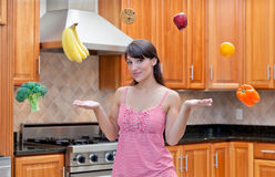 Attractive woman pondering diet and nutrition. An attractive young hispanic woman thinking about her diet, nutrition, and healthy foods such as fruits and Royalty Free Stock Image