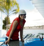 Attractive woman by pool. With hat and sunglasses Royalty Free Stock Images