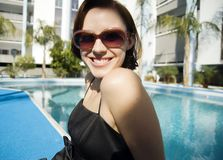 Attractive woman by pool. Wearing sunglasses Stock Photo