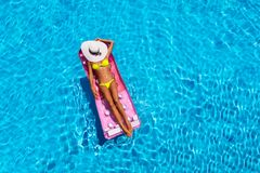 Attractive woman in the pool with a floating mattress Royalty Free Stock Photography