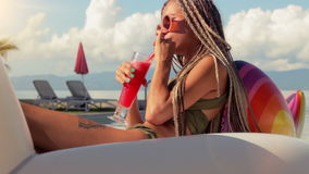Attractive woman portrait with red cocktail sitting on Inflatable unicorn in swimming pool. Attractive woman drinking red cocktail and sitting on Inflatable stock video footage