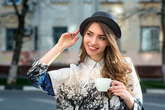 Attractive woman poses with white cup. Royalty Free Stock Image