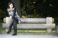 Attractive woman posing on bench in park Stock Image