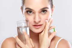 Attractive woman posing with a glass of water and vitamin capsul Stock Photos