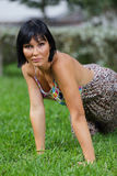 Attractive woman posing on green grass Royalty Free Stock Image