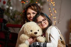 Attractive woman posing with her daughter holding a teddy bear royalty free stock photography