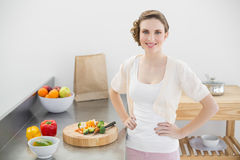 Attractive woman posing in her kitchen with hands on hips Stock Photos