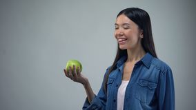 Attractive woman posing with juicy apple on grey background healthcare, template. Stock footage stock video footage