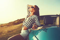 Attractive woman posing leaning on convertible car at suns Royalty Free Stock Photography