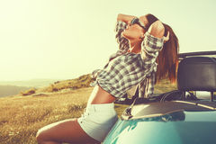 Attractive woman posing leaning on convertible car at suns Royalty Free Stock Image