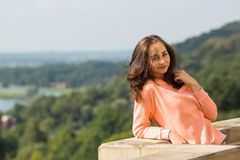 Attractive  woman posing for the photographer outdoors. Royalty Free Stock Photography