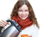 Attractive woman pouring hot water from the kettle into a cup Stock Photo