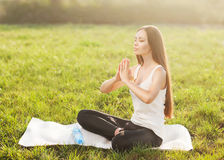 Attractive woman practices yoga in nature. Royalty Free Stock Photography